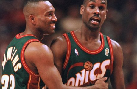 Seattle SuperSonics' Hersey Hawkins (33) tries to settle down Gary Payton in the second quarter against the Chicago Bulls Wednesday, June 5, 1996, in Chicago during Game 1 of the NBA finals. (AP Photo/Fred Jewell)