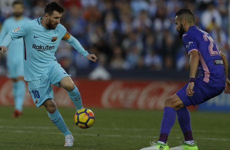 Barcelona's Lionel Messi, left, controls the ball next to Leganes' Dimitrios Siovas during the Spanish La Liga soccer match between Barcelona and Leganes at the Butarque stadium in Madrid, Saturday, Nov 18, 2017. (AP Photo/Francisco Seco)