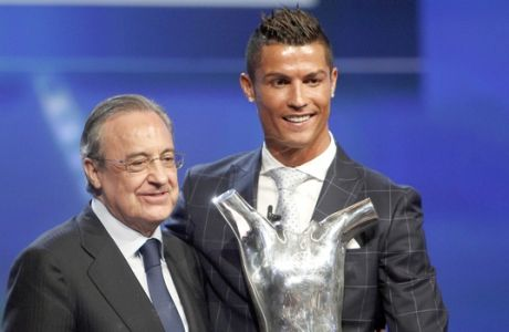 Real Madrid's forward Cristiano Ronaldo of Portugal, right, holds his best player of the year trophy, as he poses with Real Madrid's President Florentino Perez, during the UEFA Champions League draw, at the Grimaldi Forum, in Monaco, Thursday, Aug. 25, 2016. (AP Photo/Claude Paris)