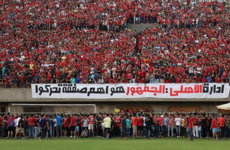 "In this July 19, 2015 photo, Ultras Ahlawy, the hardcore fan base of Al-Ahly football club,  watch players train at the Al - Ahly club in Cairo, Egypt. Ultras, whose name comes from the Latin word for beyond, started in Latin America and Europe in the 1950s and eventually made it to Arab countries, with particularly strong followings in North Africa. The first to form in Egypt, Ultras White Knights, emerged in 2007 to support the Zamalek team. Groups backing arch-rival al-Ahly and others soon followed. Arabic on the banner reads, ""the Al-Ahly administration: the fans are the most important group to be moved."" (AP Photo/Mohammed El Raai)"