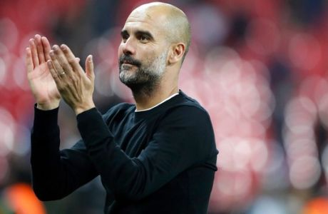 FILE - In this file photo dated Saturday, April 14, 2018, Manchester City manager Pep Guardiola applauds the fans as he walks from the pitch after the end of the English Premier League soccer match against Tottenham Hotspur at Wembley stadium in London.  Guardiola said Friday April 20, 2018, that he will speak with the club at the end of the season about extending his contract at the new Premier League champions.(AP Photo/Frank Augstein, FILE)