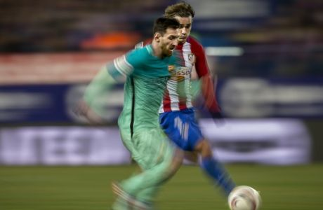 FC Barcelona's Leo Messi, left, duels for the ball with Atletico de Madrid Antoine Griezmann during a Spanish Copa del Rey semifinal first round soccer match between Atletico de Madrid and FC Barcelona at the Vicente Calderon stadium in Madrid, Spain, Wednesday, Feb. 1, 2017. (AP Photo/Daniel Ochoa de Olza)