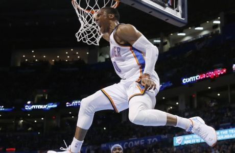 CORRECTS FINAL SCORE TO 119-94 - Oklahoma City Thunder guard Russell Westbrook (0) hangs from the basket in front of Denver Nuggets guard Ty Lawson (3) following a dunk in the third quarter of an NBA basketball game in Oklahoma City, Sunday, Feb. 22, 2015. Oklahoma City won 119-94. (AP Photo/Sue Ogrocki)