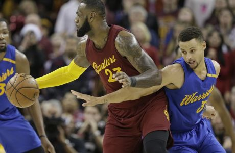 Golden State Warriors' Stephen Curry, right, puts pressure on Cleveland Cavaliers' LeBron James in the second half of an NBA basketball game, Sunday, Dec. 25, 2016, in Cleveland. (AP Photo/Tony Dejak)