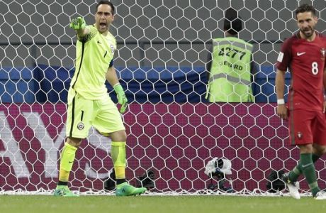 Chile goalkeeper Claudio Bravo celebrates after stopping a penalty from Portugal's Joao Moutinho, right, during the Confederations Cup, semifinal soccer match between Portugal and Chile, at the Kazan Arena, Russia, Wednesday, June 28, 2017. (AP Photo/Ivan Sekretarev)