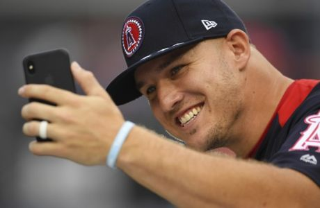 FILE - In this July 16, 2018, file photo, American League All-Star Mike Trout, of the Los Angeles Angels, takes a photo on the field ahead of the All-Star Home Run Derby at Nationals Park in Washington. A person familiar with the negotiations tells The Associated Press Tuesday, March 19, 2019, that Trout and the Angels are close to finalizing a record $432 million, 12-year contract that would shatter the record for the largest deal in North American sports history. (AP Photo/Patrick Semansky)