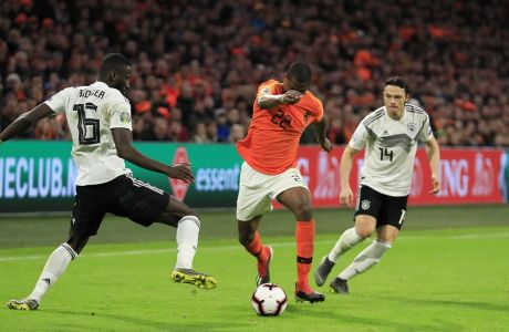 Netherlands' Denzel Dumfries, center, challenges for the ball with Germany's Antonio Rudiger, left, and Germany's Nico Schulz during the Euro 2020 group C qualifying soccer match between Netherlands and Germany at the Johan Cruyff ArenA in Amsterdam, Sunday, March 24, 2019. (AP Photo/Peter Dejong)