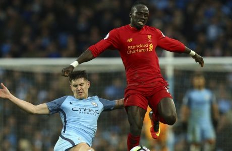 Manchester City's John Stones, left, tackles Liverpool's Sadio Mane during the English Premier League soccer match between Manchester City and Liverpool at the Etihad Stadium in Manchester, England, Sunday March 19, 2017. (AP Photo/Dave Thompson)
