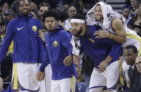 Golden State Warriors guard Stephen Curry, top right, leans on the back of JaVale McGee as players on the bench celebrate during the second half of the team's NBA basketball game against the Brooklyn Nets in Oakland, Calif., Tuesday, March 6, 2018. (AP Photo/Jeff Chiu)