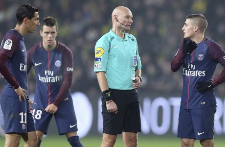 French referee Tony Chapron, center, talks to Marco Verratti, right, of Paris Saint Germain while Angel di Maria, left, listens after Chapron kicked out in retribution at Nantes defender Diego Carlos, who inadvertently clipped the referee's heels, during the French League One soccer match between Nantes and Paris Saint Germain, in Nantes, western France, Sunday, Jan. 14, 2018. The French football federation has suspended Chapron until further notice. (AP Photo/David Vincent)
