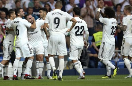 Real Madrid's Daniel Carvajal, center, celebrates with teammates after scoring their side's first goal against Getafe during a Spanish La Liga soccer match at the Santiago Bernabeu stadium in Madrid, Sunday, Aug. 19, 2018. (AP Photo/Andrea Comas)