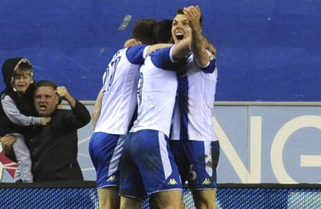 Wigan's Will Grigg celebrates with his teammates after scoring his side's opening goal during the English FA Cup fifth round soccer match between Wigan Athletic and Manchester City at The DW Stadium, Wigan, England, Monday, Feb. 19, 2018. (AP Photo/Rui Vieira)