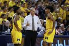 Michigan head coach John Beilein talks with Zavier Simpson, left, and Eli Brooks in the first half of an NCAA college basketball game against Indiana in Ann Arbor, Mich., Sunday, Jan. 6, 2019. (AP Photo/Paul Sancya)