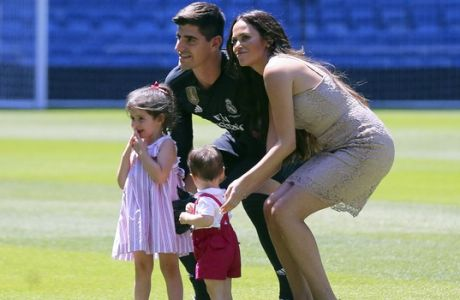 EDS NOTE: SPANISH LAW REQUIRES THAT THE FACES OF MINORS ARE MASKED IN PUBLICATIONS WITHIN SPAIN. Belgian new Real Madrid soccer player Thibaut Courtois, left, poses for the media with Marta Dominguez, the mother of his daughter Adriana and his son Nicolas, during his official presentation for Real Madrid at the Santiago Bernabeu stadium in Madrid, Thursday, August 9, 2018. Chelsea has sold a player  goalkeeper Thibaut Courtois  to Real Madrid. The Belgian was replaced by Kepa Arrizabalaga after Chelsea met the goalkeeper's 80 million euro ($93 million) buyout clause from Athletic Bilbao on Wednesday. (AP Photo/Andrea Comas)