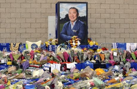 Tributes from supporters are seen outside Leicester City Football Club after a helicopter crashed Saturday killing Leicester City's owner, Thai billionaire Vichai Srivaddhanaprabha, and four other people, in Leicester, England, Monday Oct. 29 2018. The helicopter crashed in flames in a car park next to the soccer club's stadium shortly after it took off from the pitch following a Premier League game on Saturday night. (AP Photo/Rui Vieira)