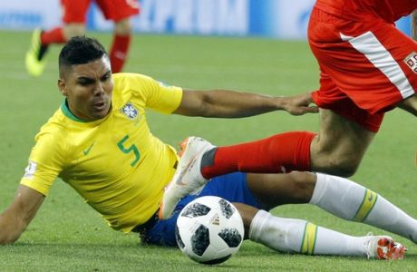 Brazil's Casemiro, left low, and Serbia's Aleksandar Mitrovic, right, challenge for the ball during the group E match between Serbia and Brazil, at the 2018 soccer World Cup in the Spartak Stadium in Moscow, Russia, Wednesday, June 27, 2018. (AP Photo/Victor R. Caivano)