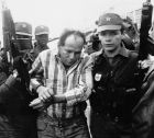 Colombian National Police escort murder suspect, Humberto Munoz, from the airport in Bogota, Colombia on July 3, 1994. Munoz was captured Saturday in Medellin and accused of shooting soccer player Andres Escobar. (AP Photo/Henry Molano)