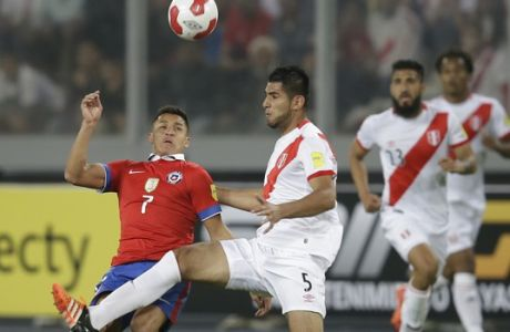 Chile's Alexis Sanchez, left, fights for the ball with Peru's Carlos Zambrano during a 2018 Russia World Cup qualifying soccer match in Lima, Peru, Tuesday, Oct. 13, 2015. (AP Photo/Martin Mejia)