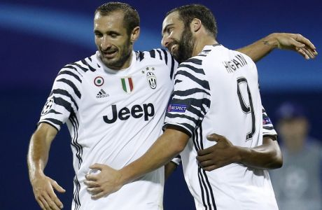 Juventus's Gonzalo Higuain, right, celebrates with team mate Giorgio Chiellini, left, after scoring his side's second goal during the Champions League Group H soccer match between Dinamo Zagreb and Juventus, at Maksimir stadium in Zagreb, Croatia, Tuesday, Sept. 27, 2016. (AP Photo/Darko Bandic)