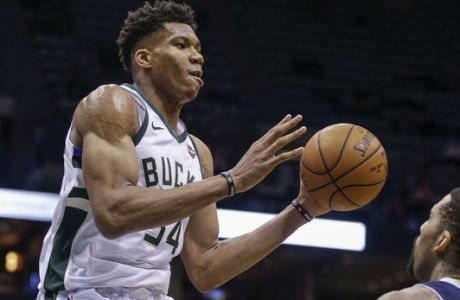 Milwaukee Bucks' Giannis Antetokounmpo looks to pass the ball over Denver Nuggets' Wilson Chandler during the second half of an NBA basketball game Thursday, Feb. 15, 2018, in Milwaukee. The Nuggets defeated the Bucks 134-123. (AP Photo/Tom Lynn)