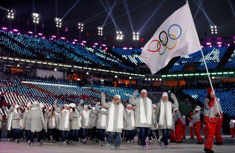 Ρώσοι αθλητές παρελαύνουν με τη σημαία της Διεθνούς Ολυμπιακής Επιτροπής αντί της ρωσικής εξαιτίας αποκλεισμού της πατρίδας τους λόγω παραβάσεων των κανονισμών περί ντόπινγκ, στους Χειμερινούς Ολυμπιακούς Αγώνες 2018, Πιόνγκτσανγκ, Παρασκευή 9 Φεβρουαρίου 2018