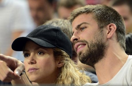 FILE - In this Sept. 9, 2014, file photo, FC Barcelona's player Gerard Pique, right, and Colombian singer Shakira attend a Basketball World Cup quarterfinal match between Slovenia and United States at the Palau Sant Jordi in Barcelona, Spain. Shakira announced Monday Jan. 19, 2014, that the couple celebrated a virtual baby shower through UNICEF to help poor children around the world. (AP Photo/Manu Fernandez, File)