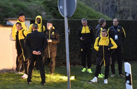 Head coach Thomas Tuchel, right, and players of Borussia Dortmund stand outside their team bus after it was damaged in an explosion before the Champions League quarterfinal soccer match between Borussia Dortmund and AS Monaco in Dortmund, western Germany, Tuesday, April 11, 2017.  (AP Photo/Martin Meissner)