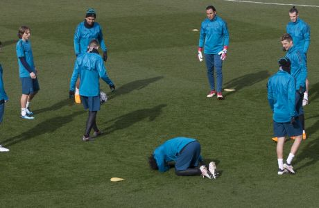 Real Madrid's Marcelo kneels on the pitch after taking a knock during a training session in Madrid, Spain, Tuesday Feb. 13, 2018. Real Madrid will play Paris Saint Germain Wednesday in a Round of 16, 1st leg Champions League soccer match. (AP Photo/Paul White)