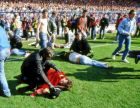 FILE - In this April 15, 1989 file photo police, stewards and supporters care for wounded supporters on the field at Hillsborough Stadium, in Sheffield, England.  The Hillsborough disaster was a fatal human crush during an English FA Cup semi-final soccer match between Liverpool and Nottingham Forest at Hillsborough Stadium on 15 April 1989, where 96 people died and many hundreds injured, and is widely considered the worst disaster in British sporting history. (AP Photo, File)