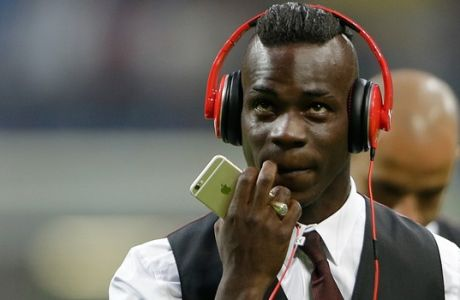 AC Milan's Mario Balotelli wears earphones prior to the start of a Serie A soccer match between Inter Milan and AC Milan, at the San Siro stadium in Milan, Italy, Sunday, Sept. 13, 2015. (AP Photo/Luca Bruno)