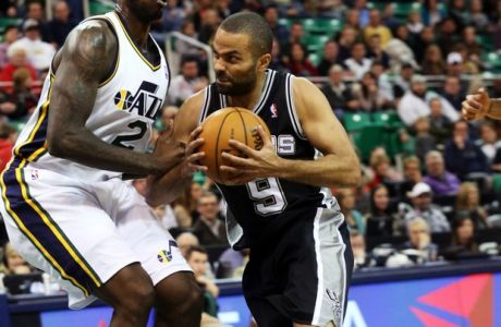 San Antonio Spurs' Tony Parker (9) drives the basket as Utah Jazz's Marvin Williams (2) defends in the first half of an NBA basketball game on Saturday, Dec. 14, 2013, in Salt Lake City. San Antonio won the game 100-84. (AP Photo/Kim Raff)
