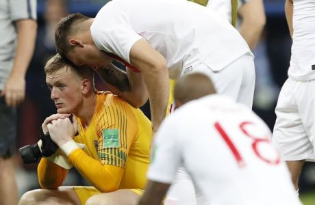 England goalkeeper Jordan Pickford, left, reacts at the end of the semifinal match between Croatia and England at the 2018 soccer World Cup in the Luzhniki Stadium in Moscow, Russia, Wednesday, July 11, 2018. (AP Photo/Rebecca Blackwell)