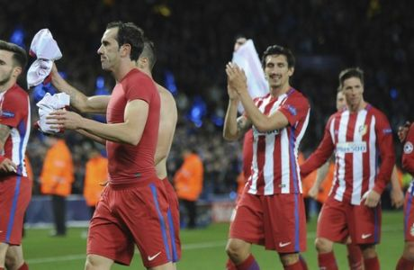 Atletico Madrid players walk to throw their shirts to their fans as they celebrate following the Champions League quarterfinal second leg soccer match between Leicester City and Atletico Madrid at King Power Stadium, Leicester, England, Tuesday, April 18, 2017. (AP Photo/Rui Vieira)