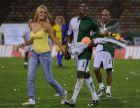 Colombia's model Claudia Perlwitz, left, and Colombia's soccer star Faustino Asprilla walk at the end of Asprilla's retirement match in Medellin, Colombia, Saturday, July 4, 2009. (AP Photo/Luis Benavides)