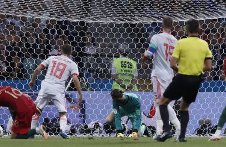 Spain goalkeeper David De Gea, in green, looks round as the ball goes into the net as Portugal's Cristiano Ronaldo, right scores his sides 2nd goal of the game during the group B match between Portugal and Spain at the 2018 soccer World Cup in the Fisht Stadium in Sochi, Russia, Friday, June 15, 2018. (AP Photo/Manu Fernandez)