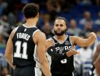 San Antonio Spurs' Patty Mills, right, talks with Bryn Forbes (11) before shooting a free throw against the Orlando Magic during the first half of an NBA preseason basketball game, Friday, Oct. 12, 2018, in Orlando, Fla. (AP Photo/John Raoux)
