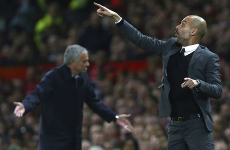 Manchester City's manager Pep Guardiola, right, gestures to his players alongside Manchester United's manager Jose Mourinho during the English League Cup soccer match between Manchester United and Manchester City at Old Trafford stadium in Manchester, England, Wednesday, Oct. 26, 2016. (AP Photo/Dave Thompson)