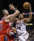 Milwaukee Bucks' Giannis Antetokounmpo goes up for a shot while being guarded by Washington Wizards' Marcin Gortat during the second half of an NBA basketball game Tuesday, Feb. 27, 2018, in Milwaukee. (AP Photo/Tom Lynn)