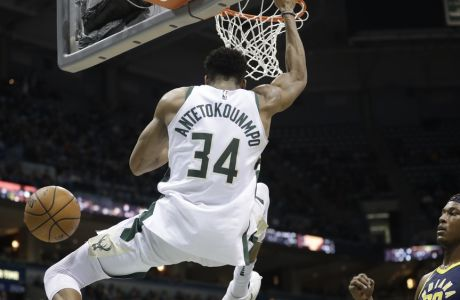 Milwaukee Bucks' Giannis Antetokounmpo dunks over Indiana Pacers' Myles Turner during the second half of an NBA basketball game Wednesday, Jan. 3, 2018, in Milwaukee. (AP Photo/Morry Gash)