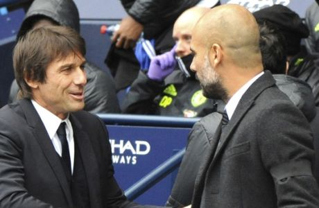 Chelsea manager Antonio Conte, left, shakes hands with Manchester City manager Josep Guardiola during the English Premier League soccer match between Manchester City and Chelsea at the Etihad Stadium in Manchester, England, Saturday, Dec. 3, 2016. (AP Photo/Rui Vieira)