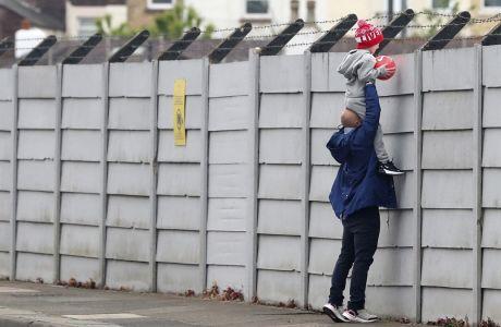 Ένας άντρας κρατάει το παιδί του ψηλά πάνω από τον φράκτη, για να μπορεί να δει μέσα στο Melwood, το προπονητικό κέντρο της Λίβερπουλ. Τη στιγμή που η Premier League έδωσε το 'οκ' για προπονήσεις σε γκρουπ των 5 παικτών χωρίς επαφή, 6 νέα κρούσματα επιβεβαιώθηκαν μετά τα τεστ που πραγματοποιήθηκαν σε παίκτες και προσωπικό των ομάδων της λίγκας. (Peter Byrne/PA via AP)