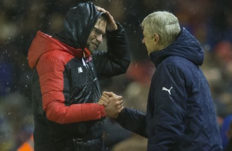Liverpool's manager Juergen Klopp, left, shakes hands with Arsenal's manager Arsene Wenger after their team's 3-3 draw in the English Premier League soccer match between Liverpool and Arsenal at Anfield Stadium, Liverpool, England, Wednesday, Jan. 13, 2016. (AP Photo/Jon Super)