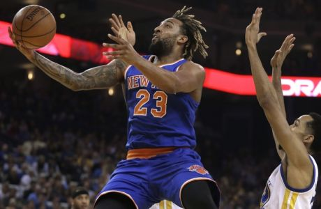 New York Knicks' Derrick Williams, left, lays up a shot past Golden State Warriors' Shaun Livingston during the first half of an NBA basketball game Wednesday, March 16, 2016, in Oakland, Calif. (AP Photo/Ben Margot)