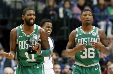 Boston Celtics' Kyrie Irving (11) reacts to being charged with a foul as Marcus Smart (36) ad Dallas Mavericks' Yogi Ferrell, rear, look on in the second half of an NBA basketball game, Monday, Nov. 20, 2017, in Dallas. (AP Photo/Tony Gutierrez)