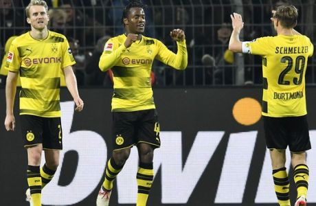 Dortmund's Michy Batshuayi, center, is celebrated after scoring the final goal in the additional time during the German Bundesliga soccer match between Borussia Dortmund and Eintracht Frankfurt in Dortmund, Germany, Sunday, March 11, 2018. Dortmund defeated Frankfurt in a dramatic 3-2. (AP Photo/Martin Meissner)