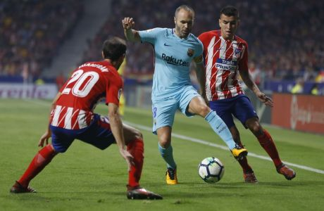 Barcelona's Andres Iniesta, centre, battles for the ball with Atletico Madrid's Juanfran, left, and Angel Correa during a Spanish La Liga soccer match between Atletico Madrid and Barcelona at the Metropolitano stadium in Madrid, Saturday, Oct. 14, 2017. The match ended in a 1-1 draw. (AP Photo/Francisco Seco)