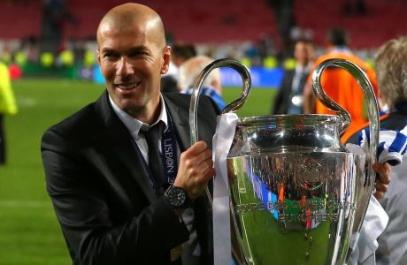 Former player Zinedine Zidane lifts the Champion League trophy, at the end of the Champions League final soccer match between Atletico Madrid and Real Madrid in Lisbon, Portugal, Saturday, May 24, 2014. Real Madrid won 4-1. (AP Photo/Andres Kudacki)