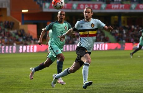 Belgiums Guillaume Gillet, right, and Portugals Joao Mario eye the ball during a friendly soccer match between Portugal and Belgium in Leiria, Portugal, Tuesday, March 29 2016. (AP Photo/Steven Governo)