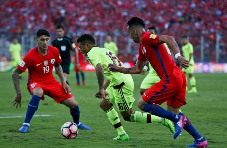 Venezuela's Darwin Machis, center, fights for the ball with Chile's Pedro Hernandez, left, and Mauricio Isla, right, during a 2018 World Cup qualifying soccer match in Santiago, Chile, Tuesday, March 28, 2017. (AP Photo/Esteban Felix)