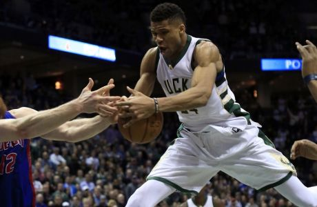 Milwaukee Bucks forward Giannis Antetokounmpo, right, grabs a rebound against the Detroit Pistons during the second half of an NBA basketball game Friday, March 31, 2017, in Milwaukee. (AP Photo/Darren Hauck)